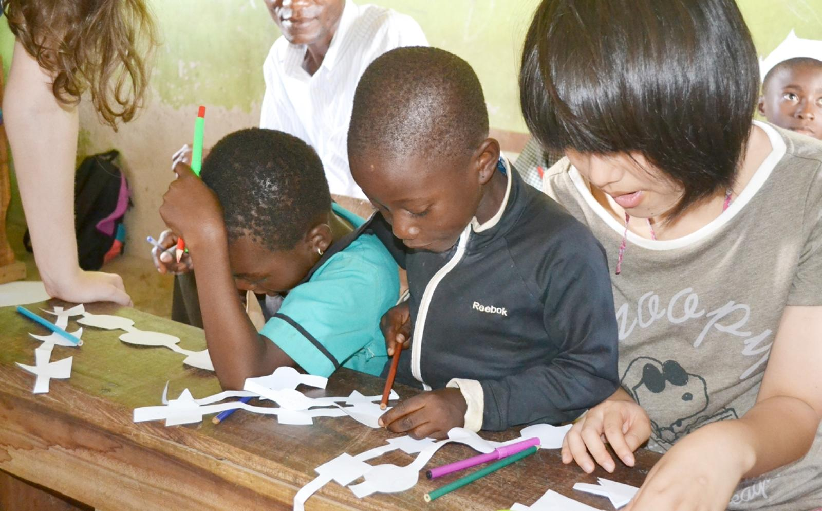 ガーナの子供たちと図画工作を行う日本人高校生ボランティア